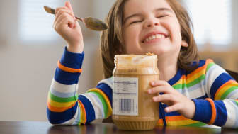 Child eating peanut butter from the jar using a spoon