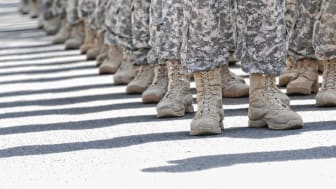 A picture from the knees down of a platoon of soldiers in fatigues.