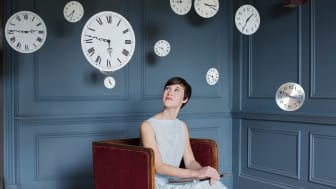A woman looks at a clock.