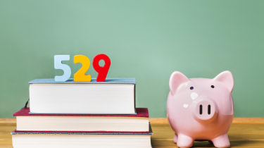 529 college savings plan theme with textbooks and piggy bank and green chalkboard background