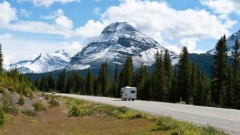An RV travels up a road in the Rocky Mountains