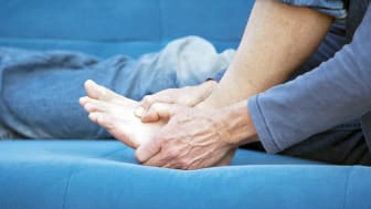 A person clutches their foot in pain