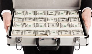An executive holds a briefcase open to show it's full of bundles of money.
