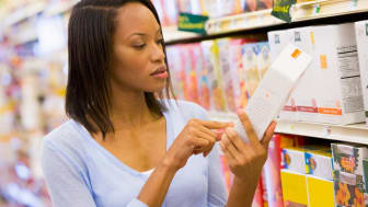 A woman reads a label on a box in a supermarket aisle