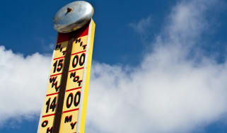 Ring the bell and win a prize.Fairground strength tester with a cloudy blue sky background. A very bright and positive image With lots of copy space.