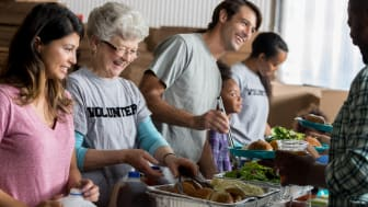Diverse family and friends serve healthy meals to the homeless in a soup kitchen. Trays of rolls and salads are on the table.