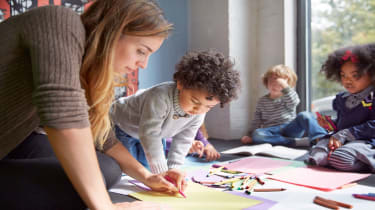 picture of childcare provider drawing on the floor with preschool-aged children