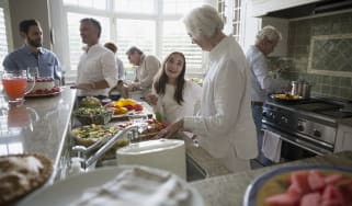 Multi-generation family cooking in kitchen