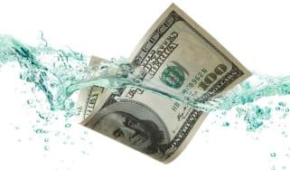 A $100 bill floats in water.