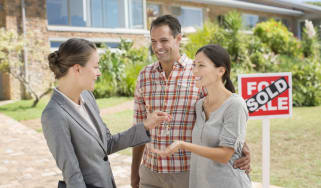 Realtor giving couple keys to new house