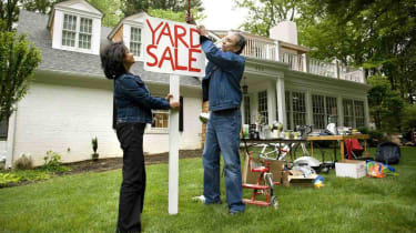 Mature couple putting up sign for Yard Sale