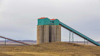 Close up of concrete coal silos and conveyors in a spring Wyoming valley landscape