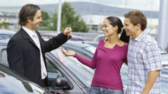 side profile of a car dealer giving car keys to a young couple