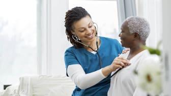 A nurse helps an elderly woman