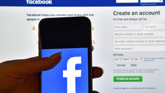 LONDON, ENGLAND - AUGUST 03: A person holds an iPhone displaying the Facebook app logo in front of a computer screen showing the facebook login page on August 3, 2016 in London, England.(Phot