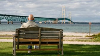 Senior man sitting on a park bench overlooking Michigan's Mackinac Bridge