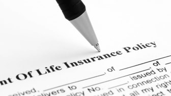 Pen being placed on a life insurance policy.
