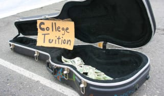 """A guitar case on a street open with some money in it and a hand-written sign that reads """"College Tuition."""""""