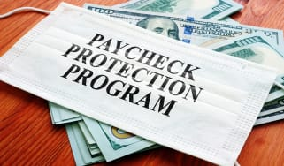 """picture of mask with """"paycheck protection program"""" written on it sitting on money"""