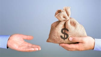 picture of one hand giving a bag of money to another hand
