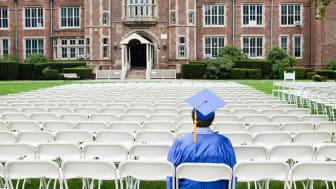 A college student sits in cap and gown ready to graduate.
