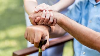 A medical professional holds hands with a nursing home resident