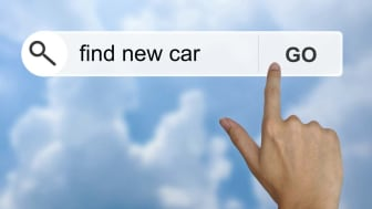 "A finger touches a computer screen that reads ""find new car"""