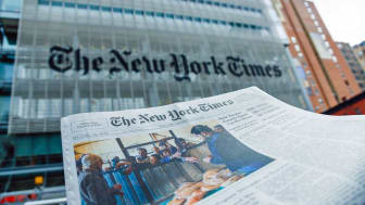 New York City, USA - May 9, 2013: A The New York Times newspaper in front of The New York Times company office building at 620 8th Avenue, Midtown Manhattan, New York City. It was completed i