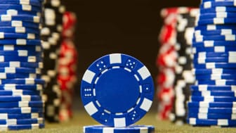 Closeup of poker chips on red felt card table surface