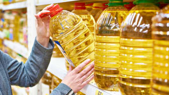 A woman takes an oversize bottle of cooking oil off a store shelf