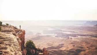 One person looks out over the canyon of Canyonlands National Park in Utah during sunset