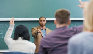 Shot of a young male teacher giving a lesson to his students on the lecture hall
