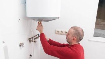 Plumber repairing an electric boiler inside home