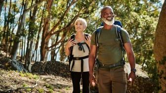 Seniors hiking wearing backpacks
