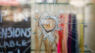 The window of a business has a bullet hole in it.