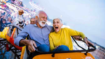 Older couple laughing while riding rollercoaster