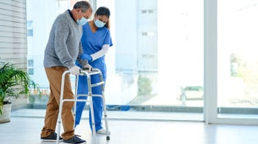 Nurse helping older gentleman use a walker; both wearing surgical masks