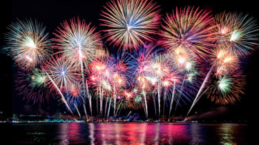 Fireworks light up the sky over a lake.