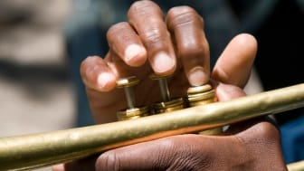 Close up of a man playing trumpet on Bourbon Street in New Orleans, Louisianaon sunny day.
