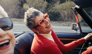 Two women laugh as they take a drive in a convertible.