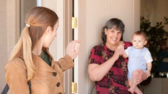 picture of mother waving bye to babysitter and young child