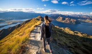 A woman walks on a mountain path.