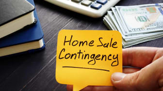 Realtor holds home sale contingency memo sign.