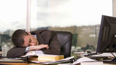 A businessman sleeps at his desk.