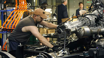 In this photo taken June 23, 2010, assemblyman Adam Metzger mounts the engine to the chassis on the 2011 GMC Sierra assembly line at the Flint GM Assembly in Flint, Mich. An industry trade gr