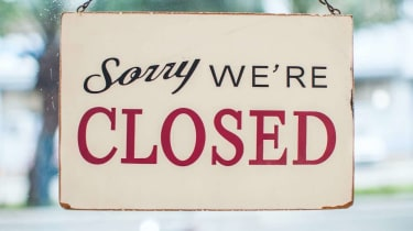 Store closed sign hanging on the glass window