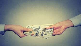 Closeup hands giving money isolated on gray wall background. Finance concept