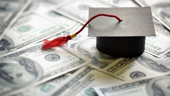 picture of a graduation cap sitting on money