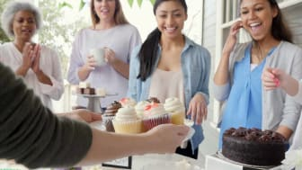 Friends laughing and enjoying time while receiving plate of cupcakes at a charity event