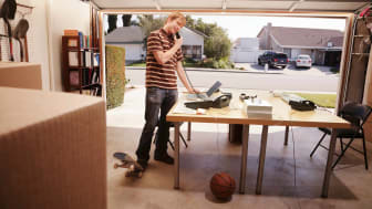 Man talking on phone in office space in garage